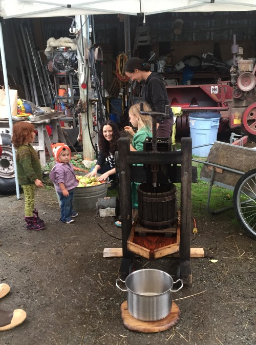 Family and friends learning about old fashion cider making