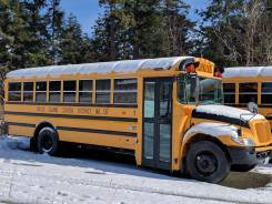 Orcas Island Public School buses parked for the day, covered in a blanket of snow.